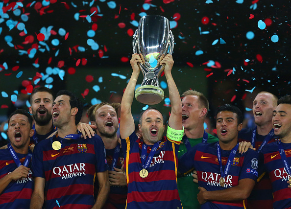 TBILISI, GEORGIA - AUGUST 11:  Andres Iniesta of Barcelona lifts the UEFA Cup trophy as Barcelona celebrate victoy during the UEFA Super Cup between Barcelona and Sevilla FC at Dinamo Arena on August 11, 2015 in Tbilisi, Georgia.  (Photo by Chris Brunskill/Getty Images)