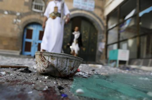 People walk past a headgear lying on the ground at the al-Balili mosque after two bombings at the mosque in Yemen's capital Sanaa, September 24, 2015. REUTERS/Khaled Abdullah