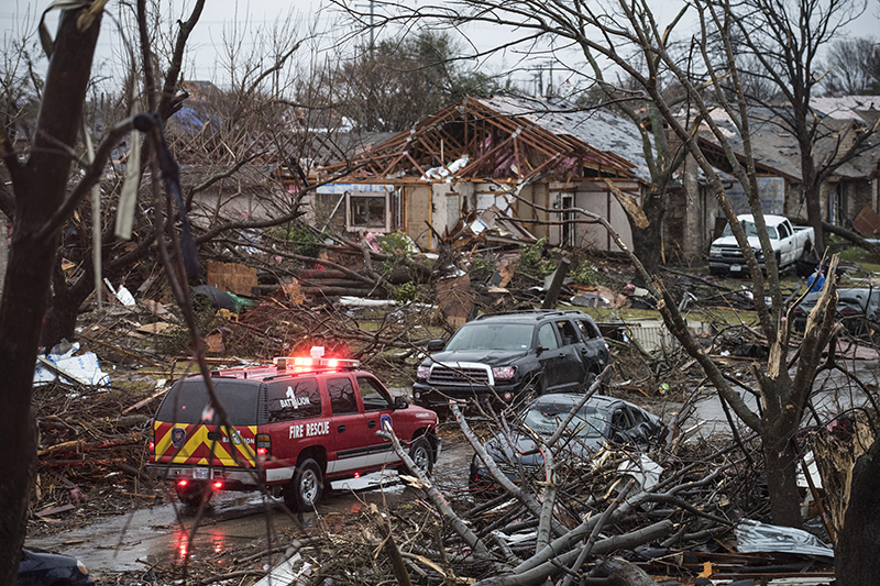 An emergency vehicle drives through a neighborhood in Rowlett, Texas, Sunday, Dec. 27, 2015, the morning after it was struck by a tornado. At least 11 people died and dozens were injured in apparently strong tornadoes that swept through the Dallas area and caused substantial damage this weekend. (AP Photo/Rex C. Curry)