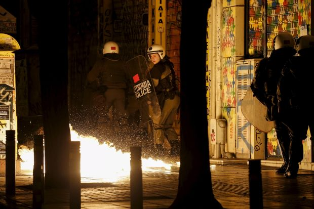 A petrol bomb explodes next to a riot police officer during clashes with hooded youth in Athens