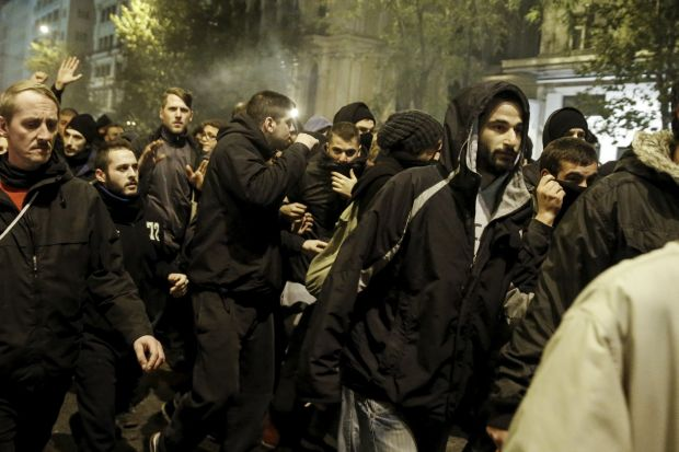 Protesters flee from tear gas thrown by riot police during clashes in Athens