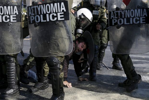 "Riot police detain a farmer during a protest against planned tax increases in Athens, Greece in this November 18, 2015 file photo. Euro zone finance ministers are expected to meet this week to discuss Greek reform implementation.    REUTERS/Alkis Konstantinidis/FilesGLOBAL BUSINESS WEEK AHEAD PACKAGE - SEARCH ""BUSINESS WEEK AHEAD DEC 7"" FOR ALL IMAGES"