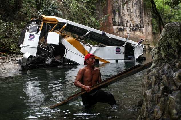 A passenger bus lays in a ravine after falling off the road in Atoyac, Veracruz state, Mexico, Sunday, Jan. 10, 2016. The bus, belonging to the Paso del Toro line, was carrying members of a football team and their relatives along the road connecting the cities of Camaron and Cordoba. According to authorities, at least 20 people were killed and 25 were injured. (AP Photo/Felix Marquez)