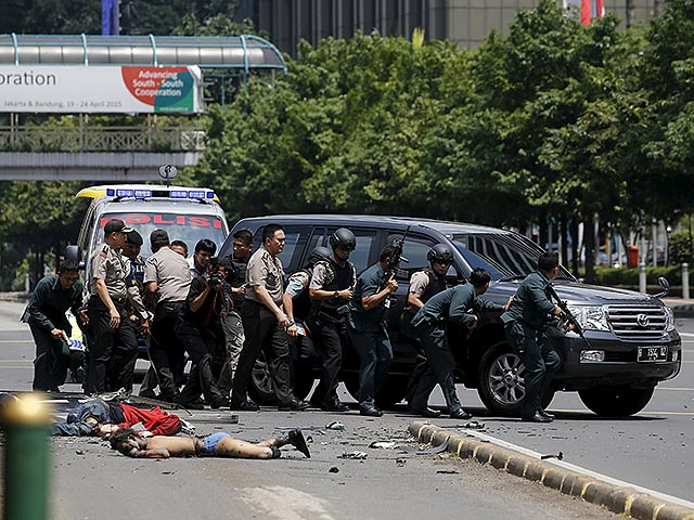 Dead bodies are seen as Indonesian police hold rifles while walking behind a car for protection in Jakarta