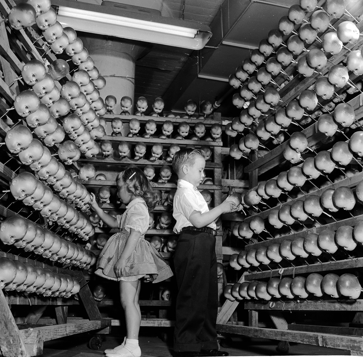 circa 1955:  A young boy and girl inspecting dolls' heads at the Ideal Toy Company in Jamaica, Long Island, USA. The company is one of the largest toy manufacturers in the world.  (Photo by Orlando /Three Lions/Getty Images)