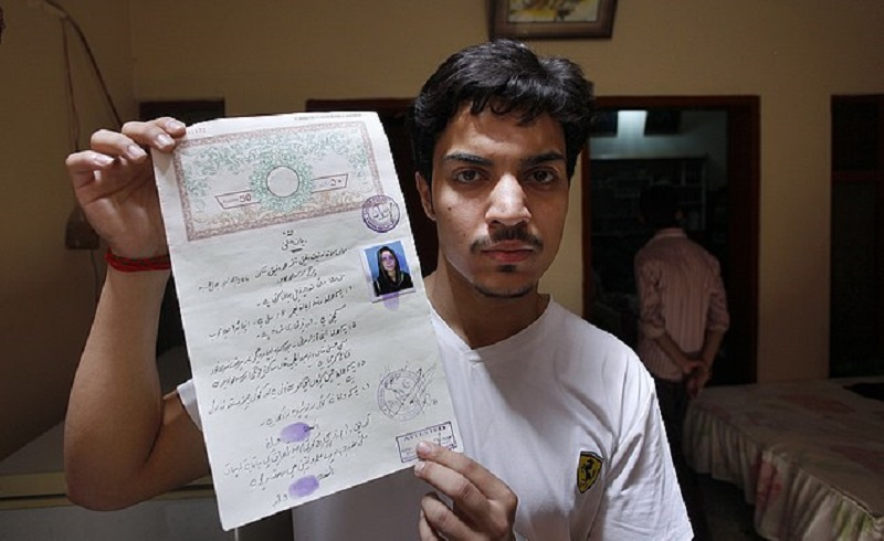 Hassan Khan, husband of Zeenat Rafiq, who was burned alive, allegedly by her mother, shows his marriage certificate to media at his home in Lahore, Pakistan Wednesday, June 8, 2016. A Pakistani woman was arrested Wednesday after dousing her daughter with kerosene and burning her alive, allegedly because the girl had defied her family to marry a man she was in love with, police said. (AP Photo/K.M. Chaudary)