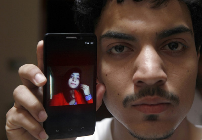 Hassan Khan shows the picture of his wife Zeenat Rafiq, who was burned alive, allegedly by her mother, on a mobile phone at his home in Lahore, Pakistan Wednesday, June 8, 2016. A Pakistani woman was arrested Wednesday after dousing her daughter with kerosene and burning her alive, allegedly because the girl had defied her family to marry a man she was in love with, police said. (AP Photo/K.M. Chaudary)