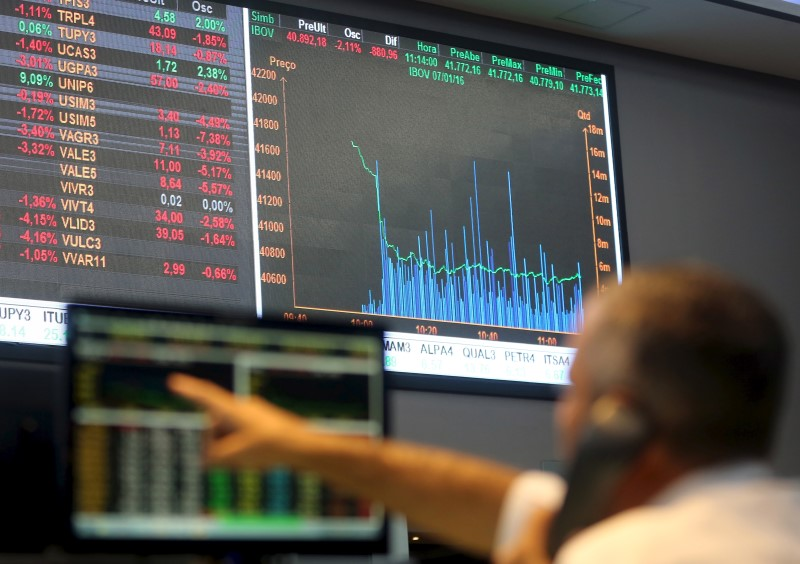 A man points to electronic board showing the graph of the recent fluctuations of market indices at the floor of Brazil's BM&F Bovespa Stock Market in Sao Paulo