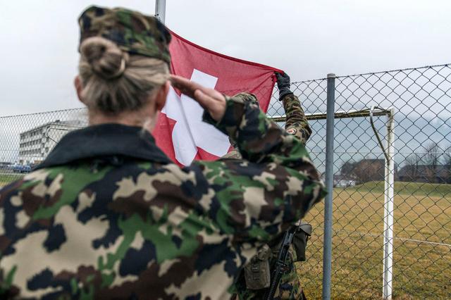 Morgens beim Antrittsverlesen wird die Schweizer Flagge gehisst, in Achtungstellug gestanden und die Fahne gegruesst,  waehrend der Ausbildung zu Swisscoy Soldaten, in der Naehe der Kaserne in Stans, aufgenommen am 5. Maerz 2014. Die SWISSCOY ist der Verband der Schweizer Armee im Kosovo. Er wird im Rahmen der friedensfoerdernden Militaermission KFOR der NATO im Kosovo mit einem Kontingent von maximal 220 Personen von der Schweiz zur Verfuegung gestellt und finanziert. Die Ausbildung dauert je nach Funktion bis zu 3 Monate. (KEYSTONE/Christian Beutler) Soldiers of the Swiss Army gather for the morning company formation, where the Swiss flag is hissed, during their training to be Swisscoy soldiers, near the casern of Stans, Switzerland, March 5, 2014. The Swisscoy is an association of the Swiss Army in Kosovo. It is provided as part of the KFOR of NATO military mission to promote peace. The association contains a contingent of more than 220 people who are available and funded from Switzerland. (KEYSTONE/Christian Beutler)