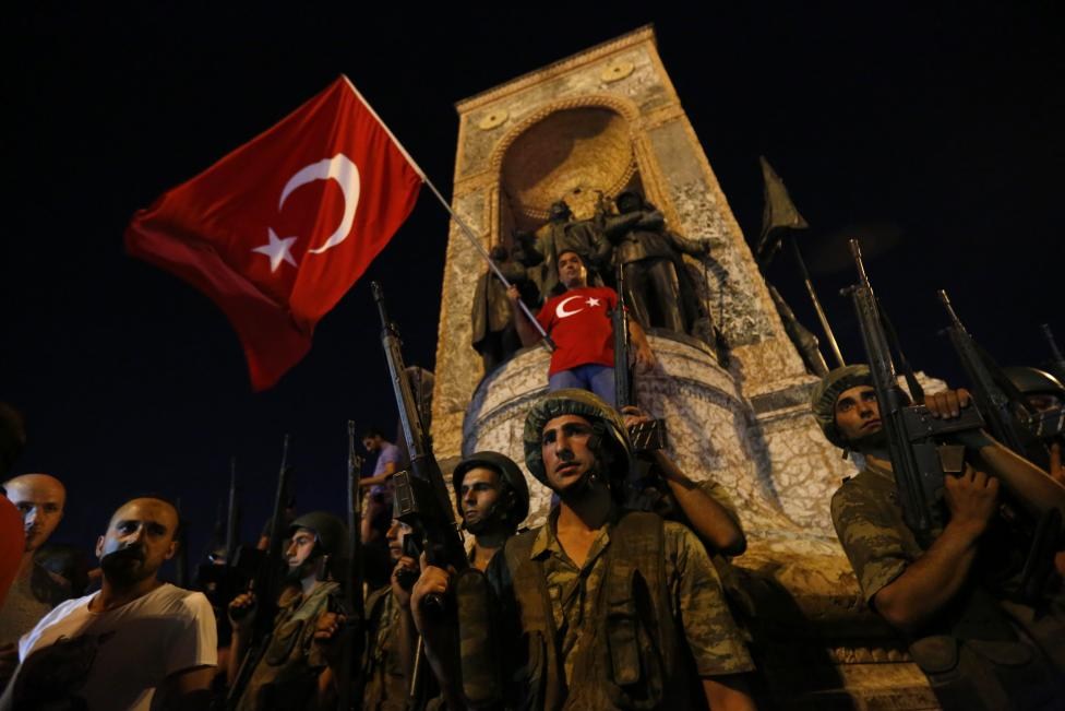 Turkish military stand guard near the the Taksim Square as peiple wave with Turkish flags in Istanbul, Turkey, July 16, 2016. REUTERS/Murad Sezer