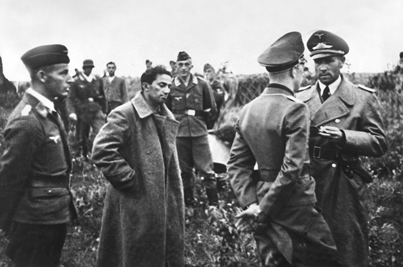 The first son of Josef Stalin, Yakov Dzhugashvili waits, after his capture on the Eastern Front, on a German airfield for his transfer to the rear for a hearing. Around him, German air force officers.