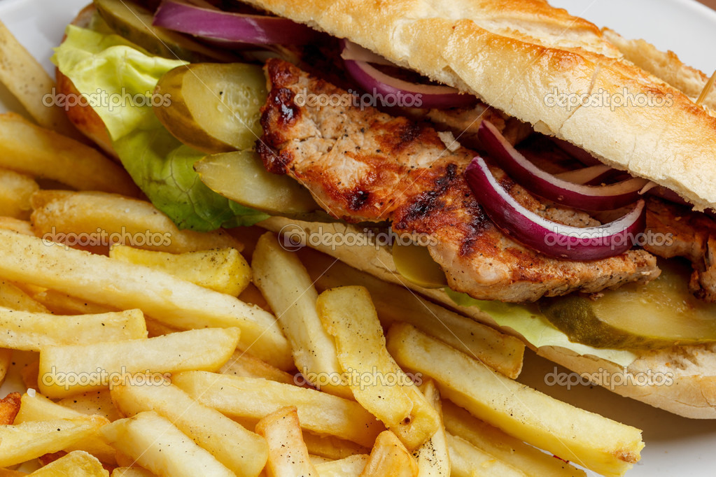 Close up of grilled pork sandwich with french fries
