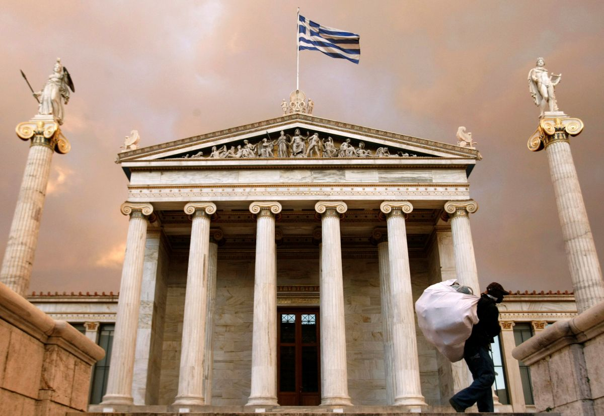 A street vendor carries his belongings in front of the Athens' Academy, Athens, Greece, December 23, 2008.     REUTERS/Yiorgos Karahalis/File Photo