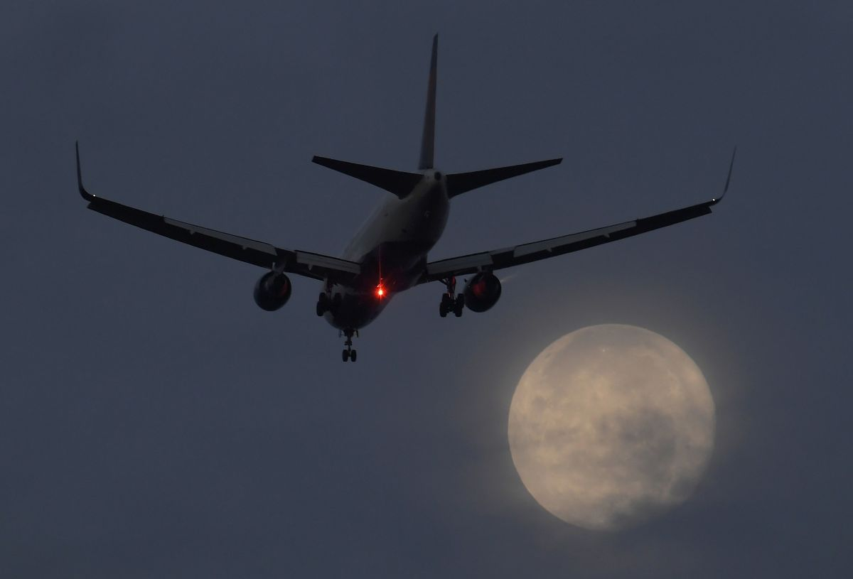 A passenger aircraft makes it's landing approach to Heathrow airport in front of a