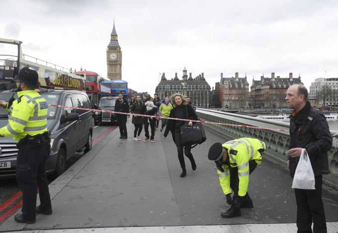 A woman ducks under a police tape after an incident on Westminster Bridge in London, March 22, 2017.  REUTERS/Toby Melville