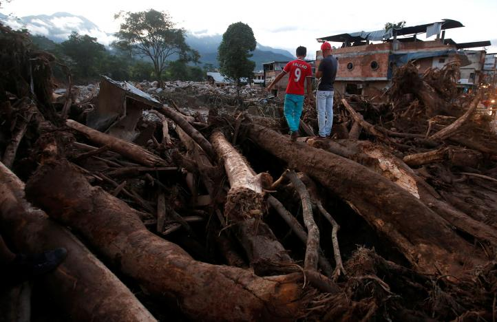 Men look at a destroyed area afterwards heavy rains caused several rivers to overflow, pushing sediment and rocks into buildings and roads in Mocoa, Colombia April 1, 2017. REUTERS/Jaime Saldarriaga