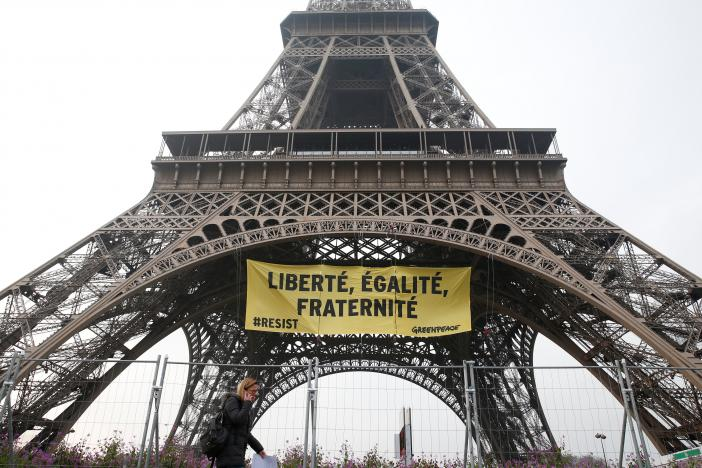 A woman passes by as activists from the environmentalist group Greenpeace unfurl a giant banner on the Eiffel Tower which reads