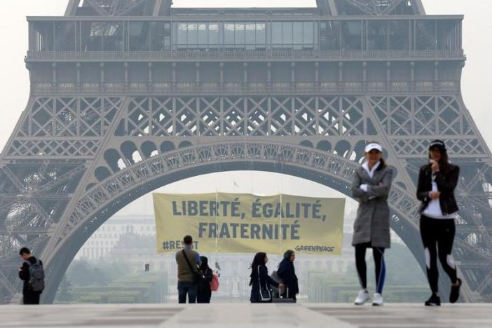 People walk at Trocadero square as activists from the environmentalist group Greenpeace unfurl a giant banner on the Eiffel Tower which reads